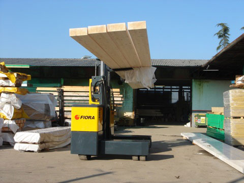 Orderly outdoor lumber and supply yard serviced with an outdoor electric sideloader